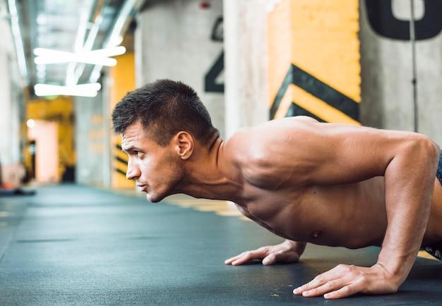 Seitenansicht eines muskulösen jungen mannes, den das handeln drückt, ups Kostenlose Fotos
