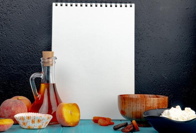 Seitenansicht eines skizzenbuchs und frisch gereifter pfirsiche getrockneter aprikosenhüttenkäse und olivenöl in einer glasflasche auf schwarz Kostenlose Fotos