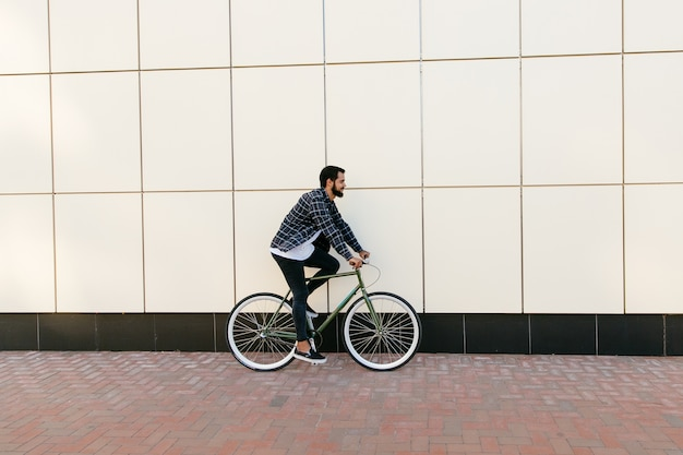 Seitenansicht eines stilvollen bärtigen mannes, der fahrrad auf die stadtstraße fährt. Kostenlose Fotos