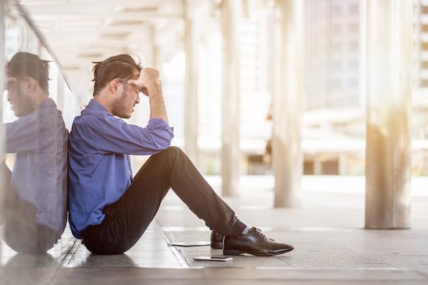 Seitenansicht eines traurigen mannes mit einer hand auf dem kopf, der im traurigen geschäftsverliererkonzept des büros sitzt Premium Fotos