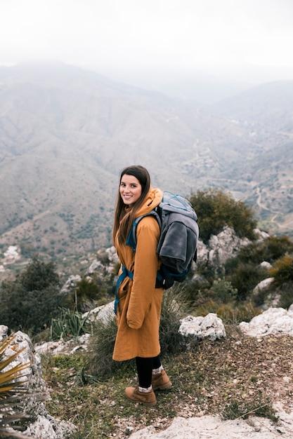 Seitenansicht eines weiblichen wanderers mit ihrem rucksack, der auf bergen wandert Kostenlose Fotos