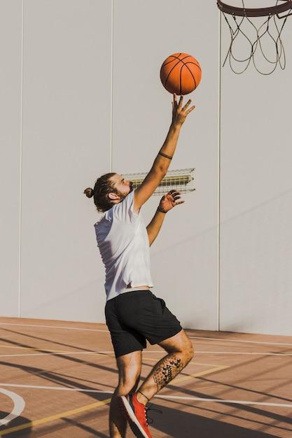 Seitenansicht eines werfenden basketballs des mannes im band Kostenlose Fotos