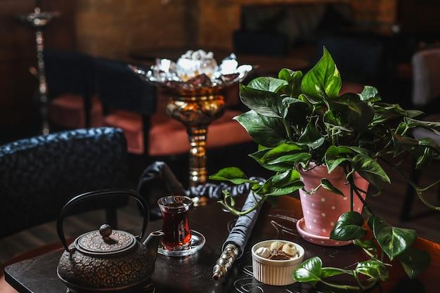 Seitenansicht eisenteekanne mit einem glas tee und einer topfpflanze auf dem tisch Kostenlose Fotos