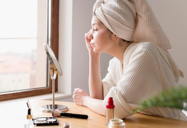 Seitenansicht frau, die eyeliner anwendet Kostenlose Fotos