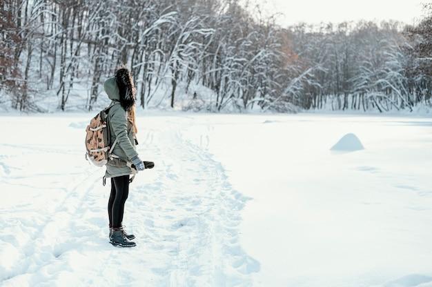 Seitenansicht frau mit rucksack am wintertag Kostenlose Fotos