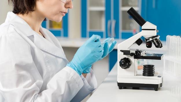 Seitenansicht frau unter verwendung eines mikroskops Kostenlose Fotos