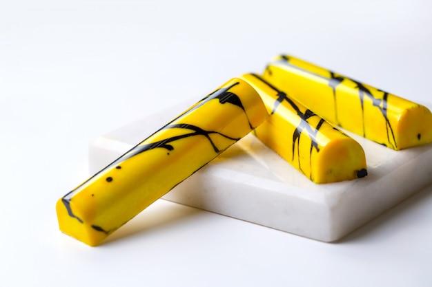 Seitenansicht gelb im schwarzen fleck praline auf weißem stand Kostenlose Fotos