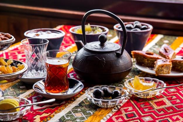 Seitenansicht gusseisen teekanne mit marmelade und einer tasse tee Kostenlose Fotos