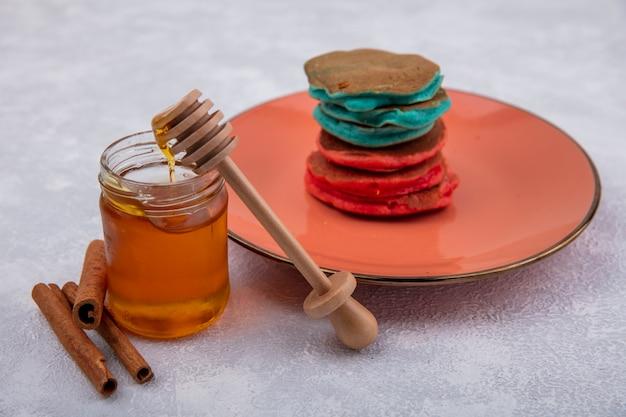 Seitenansicht honig in einem glas mit einem holzlöffel zimt und bunten pfannkuchen auf einem orangefarbenen teller auf einem weißen hintergrund Kostenlose Fotos