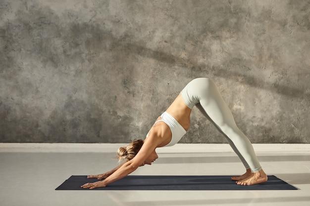 Seitenansicht in voller länge einer schönen jungen frau in sportkleidung, die drinnen trainiert, yoga-übung auf der matte praktiziert, nach unten gerichtete hundepose oder adho mukha svanasana-sonnengrußpose macht Kostenlose Fotos