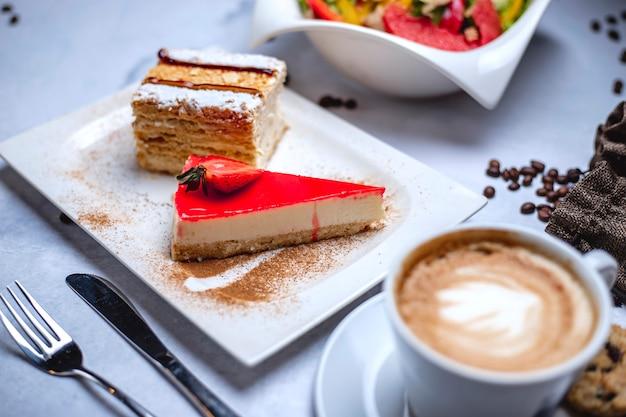 Seitenansicht käsekuchen crucker kruste mit frischkäse erdbeergelee und tasse kaffee auf dem tisch Kostenlose Fotos