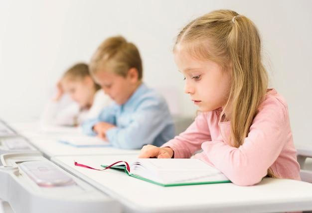Seitenansicht kinder, die ihre lektion lesen Kostenlose Fotos