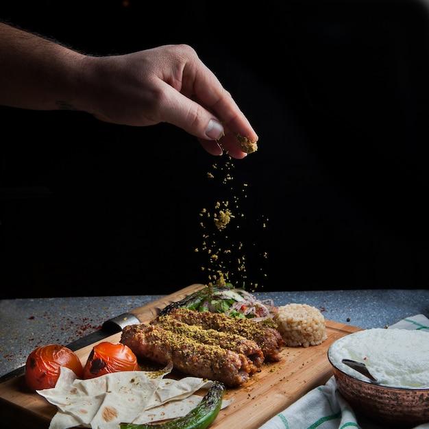 Seitenansicht lule kebab mit tomate und papier und ayran und hand fügt gewürze in servierbrett Kostenlose Fotos