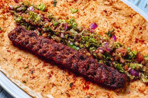 Seitenansicht lulya kebab mit roten zwiebeln geens heißem grünem pfeffersalz und pfeffer auf pita Kostenlose Fotos