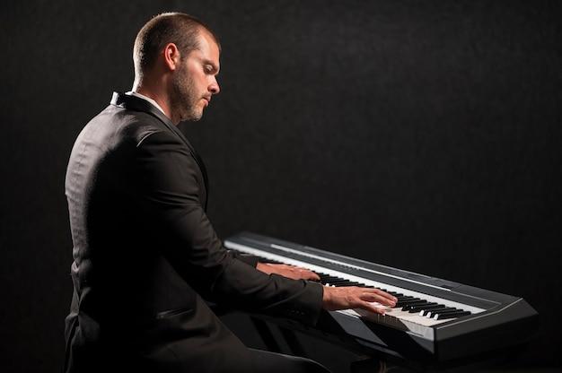 Seitenansicht person, die digitales midi-klavier spielt Kostenlose Fotos
