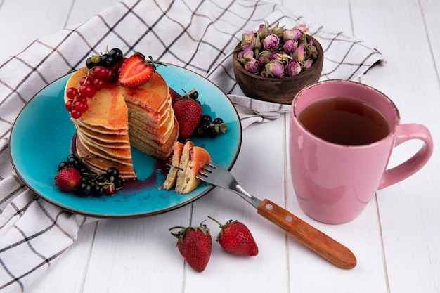 Seitenansicht pfannkuchen mit erdbeeren der schwarzen und roten johannisbeeren mit einer gabel auf einem teller mit einer tasse tee auf einem weißen karierten handtuch Kostenlose Fotos