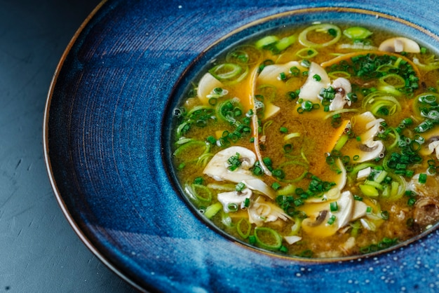 Seitenansicht pilzsuppe und frühlingszwiebeln in einem teller Kostenlose Fotos