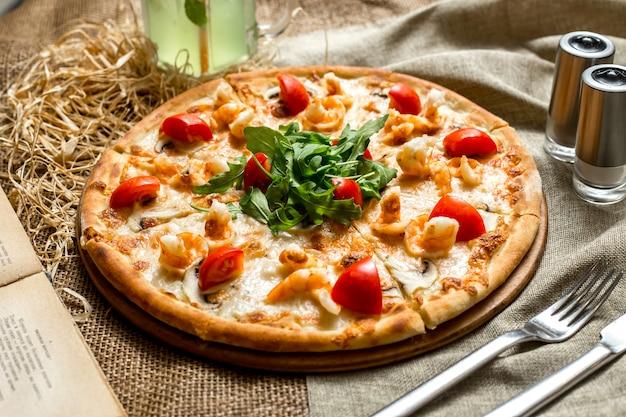 Seitenansicht pizza mit garnelen und pilzen tomaten und rucola und mit einem alkoholfreien getränk Kostenlose Fotos