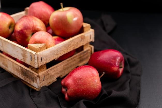 Seitenansicht rote äpfel in kiste mit schwarzem tuch Kostenlose Fotos