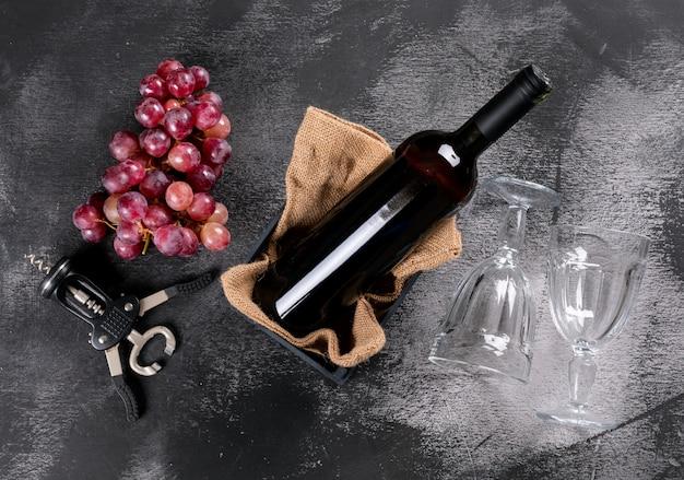 Seitenansicht rotwein mit traube in kiste mit sackleinen auf schwarzem stein horizontal Kostenlose Fotos