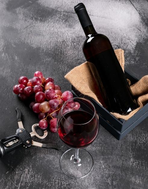 Seitenansicht rotwein mit traube in kiste mit sackleinen auf schwarzem stein vertikal Kostenlose Fotos