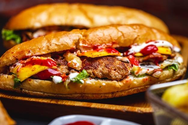 Seitenansicht sandwich weißbrot mit gegrilltem fleisch schnitzel käse salat pommes frites mayo und ketchup auf einem boardjpg Kostenlose Fotos