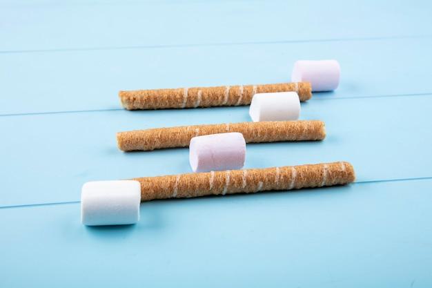 Seitenansicht von bonbons und knusprigen stöcken auf blauem hintergrund Kostenlose Fotos