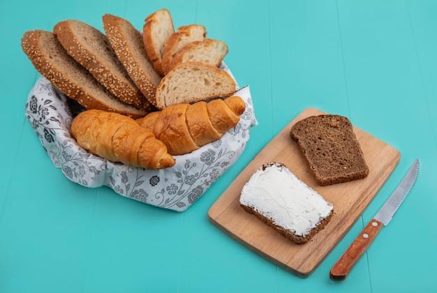 Seitenansicht von broten als geschnittenes entkerntes cob-baguette und croissant in schüssel und roggenbrot, die mit käse auf schneidebrett mit messer auf blauem hintergrund verschmiert wurden Kostenlose Fotos