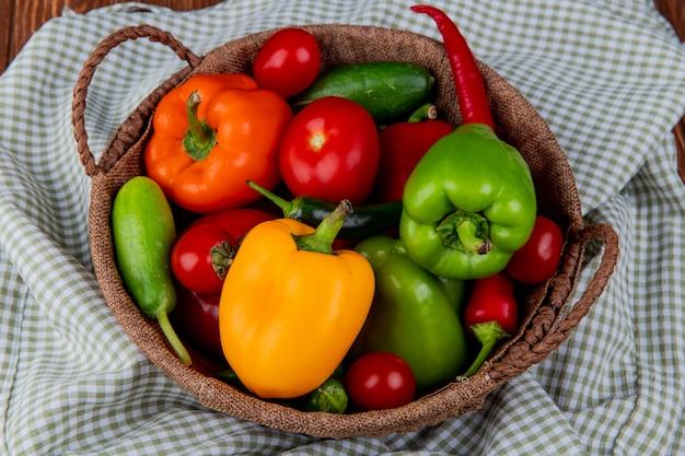 Seitenansicht von buntem paprika-paprika-tomaten und gurken des frischen gemüses in einem weidenkorb auf kariertem stoff Kostenlose Fotos
