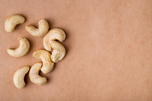 Seitenansicht von cashewnüssen auf altem papierbeschaffenheitshintergrund mit kopienraum Kostenlose Fotos