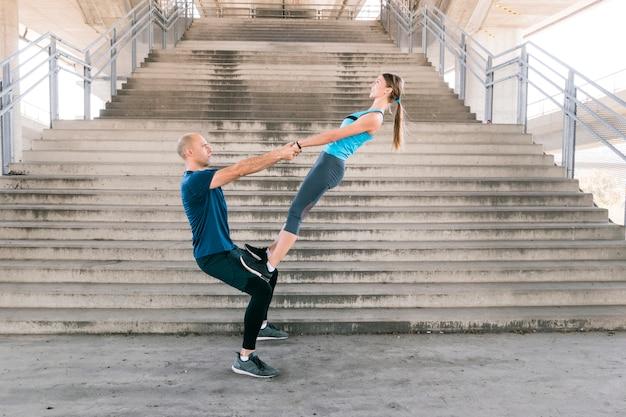 Seitenansicht von den sportiven jungen paaren, die übung vor treppenhaus tun Kostenlose Fotos
