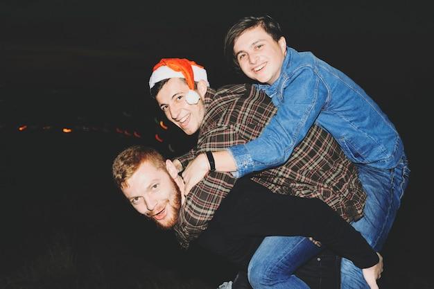 Seitenansicht von drei jungen männern im lässigen outfit, die lächeln und kamera betrachten, während spaß während der weihnachtsfeier in der dunklen nacht in der landschaft haben Premium Fotos