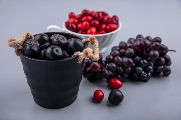 Seitenansicht von dunkelvioletten schwarzdornfrüchten auf einem schwarzen korb mit kornelkirschenbeeren auf einer tasse und trauben lokalisiert auf einem grauen hintergrund Kostenlose Fotos