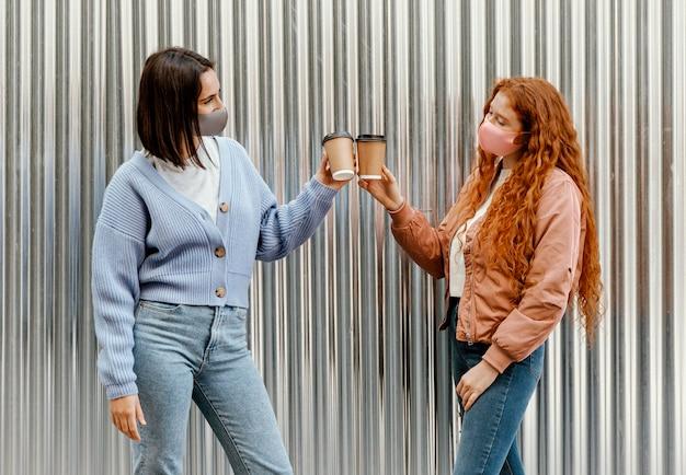 Seitenansicht von freundinnen mit gesichtsmasken im freien, die mit kaffeetassen jubeln Kostenlose Fotos