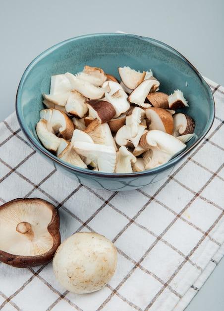 Seitenansicht von geschnittenen pilzen in einer schüssel auf karierter serviette auf hellblau Kostenlose Fotos