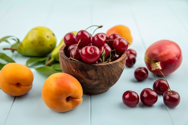 Seitenansicht von kirschen in schüssel und muster von birnen aprikosen pfirsichkirschen mit blättern auf blauem hintergrund Kostenlose Fotos