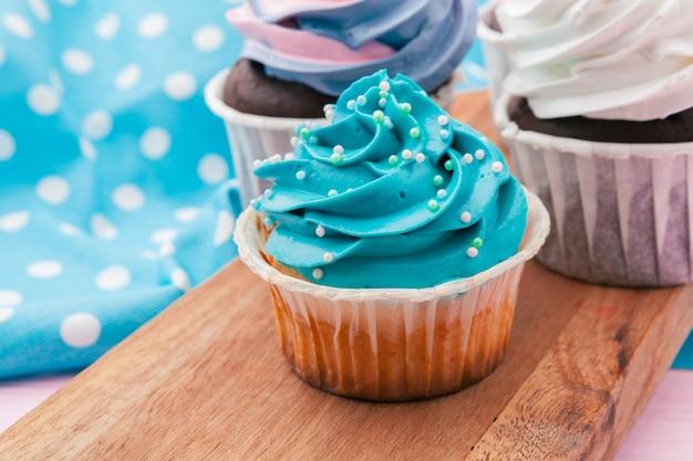 Seitenansicht von leckeren kleinen kuchen mit sortiertem aroma. auf den tisch geschossen Premium Fotos