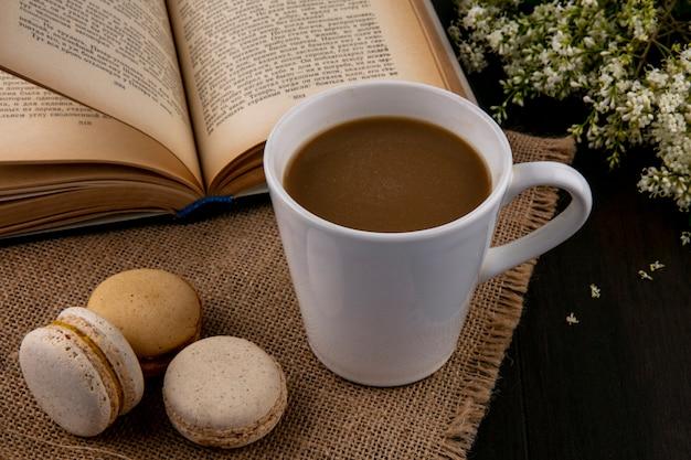Seitenansicht von macarons mit einer tasse kaffee auf einer beigen serviette mit einem offenen buch und blumen auf einer schwarzen oberfläche Kostenlose Fotos