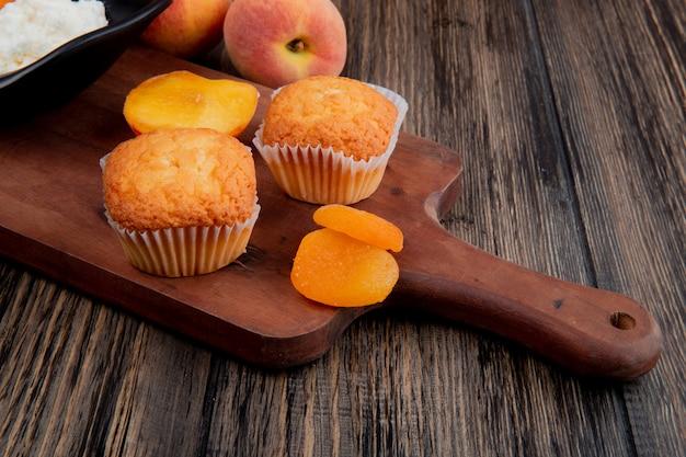 Seitenansicht von muffins mit getrockneten aprikosen auf holzschneidebrett und frischen pfirsichen auf rustikalem Kostenlose Fotos