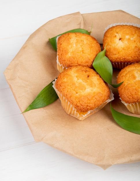 Seitenansicht von muffins mit grünen blättern auf handwerklichem braunem papier auf weißem rustikalem holz Kostenlose Fotos