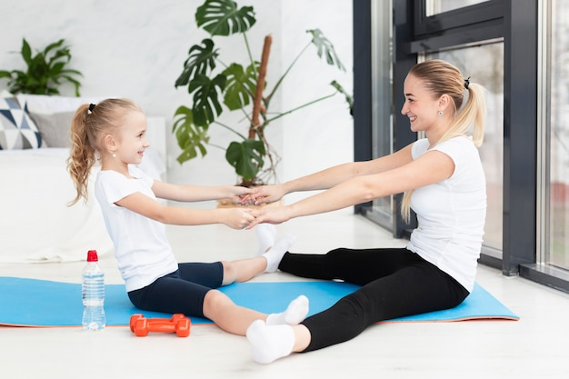 Seitenansicht von mutter und tochter, die auf yogamatte trainieren Kostenlose Fotos