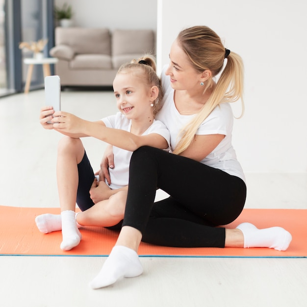 Seitenansicht von mutter und tochter, die selfie auf yogamatte nehmen Kostenlose Fotos