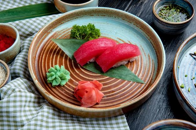 Seitenansicht von nigiri-sushi mit thunfisch auf bambusblatt, serviert mit eingelegten ingwerscheiben und wasabi auf einem teller Kostenlose Fotos