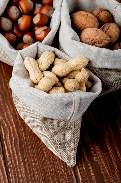 Seitenansicht von nüssen in säcken walnüssen erdnüssen und haselnüssen in der schale auf hölzernem hintergrund Kostenlose Fotos
