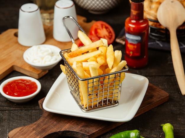 Seitenansicht von pommes frites im metalldrahtkorb Kostenlose Fotos
