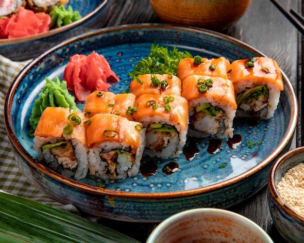 Seitenansicht von sushi-rollen mit lachsaal-avocado und frischkäse auf einem teller mit ingwer und wasabi Kostenlose Fotos