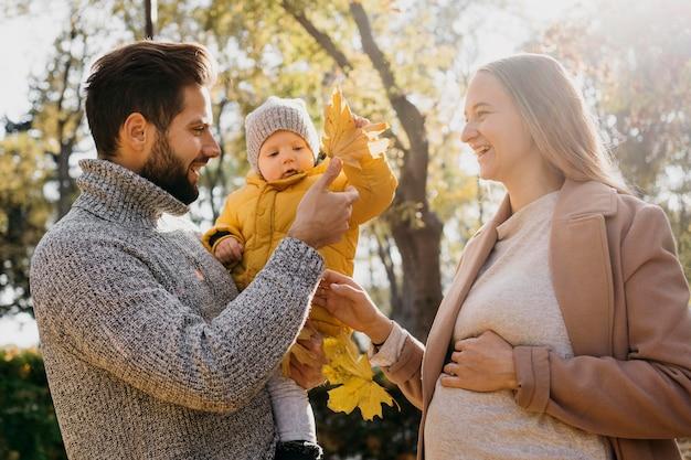 Seitenansicht von vater und mutter mit baby im freien Kostenlose Fotos