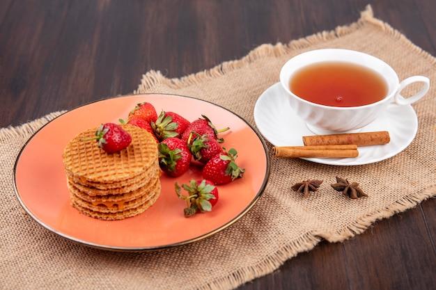 Seitenansicht von waffelkeksen und erdbeeren in teller und tasse tee mit zimt auf untertasse auf sackleinen und holz Kostenlose Fotos