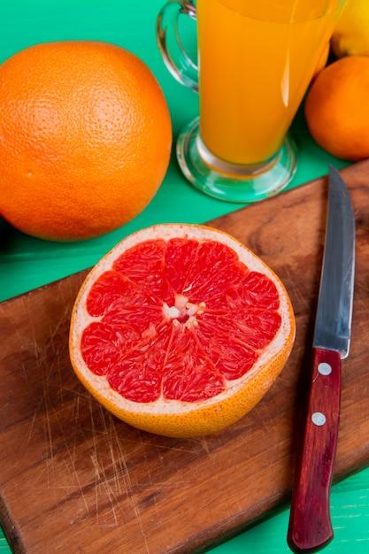 Seitenansicht von zitrusfrüchten als grapefruit mit messer auf schneidebrett und orangen-mandarine mit orangensaft auf grünem hintergrund Kostenlose Fotos
