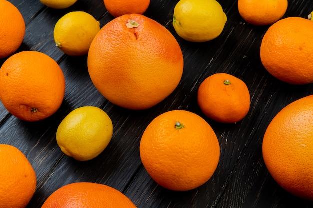 Seitenansicht von zitrusfrüchten als orange mandarinenzitrone auf hölzernem hintergrund Kostenlose Fotos